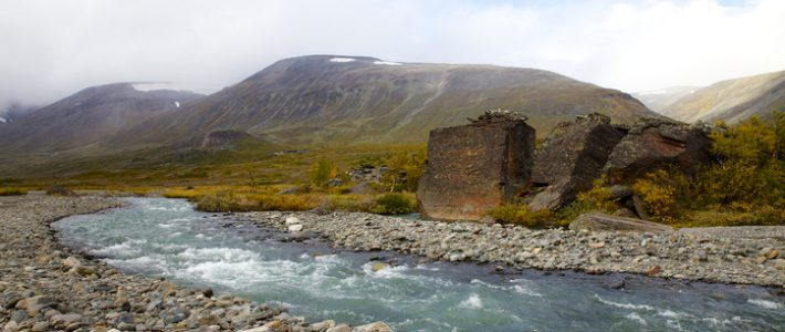 The mountain station of Kebnekaise (the highest mountain in Sweden) is seen in the distance (a little left to the middle). River, big rocks and autumn colors add to the scenery.